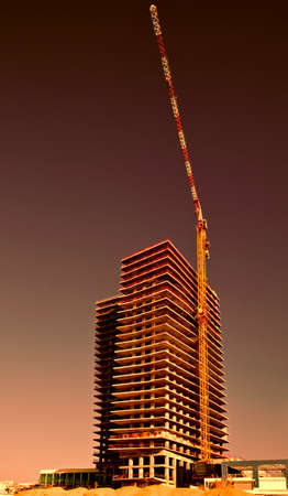 Crane and building under construction in Tel-Aviv at sunset. Industrial construction crane in Israel.