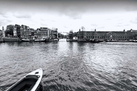 waterbus: Boat on the canal of Amsterdam in historic city centre. Amsterdam drawbridge in closed position while the water-bus is approaching to it. Black and white picture
