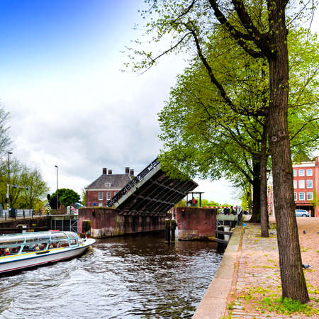 waterbus: Tourist boat on the canal of Amsterdam in historic city centre. Amsterdam drawbridge in an half-open position while the water-bus is passing by.