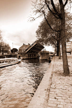 waterbus: Tourist boat on the canal of Amsterdam in historic city centre. Amsterdam drawbridge in an half-open position while the water-bus is passing by. Vintage Style Sepia photo Stock Photo