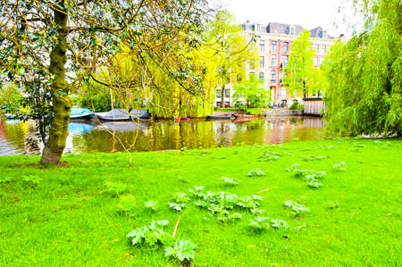 city park boat house: Urban scene in Amsterdam with typical local architecture. Embankment in the historical center of Amsterdam in the Netherlands Stock Photo