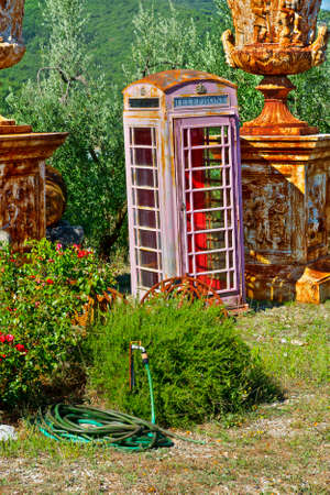Old looking public phone and ancient things in the flea-market. Junk shop with phone booth in the midst of olive grove in Italy Stock Photo