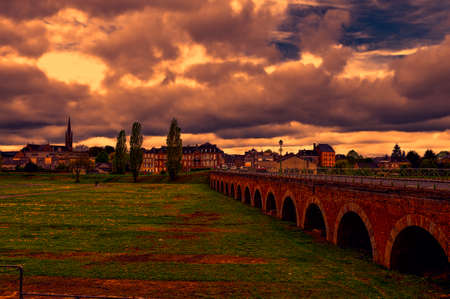 View on old houses and bridge in city of Sedan. France in rainy day at sunset