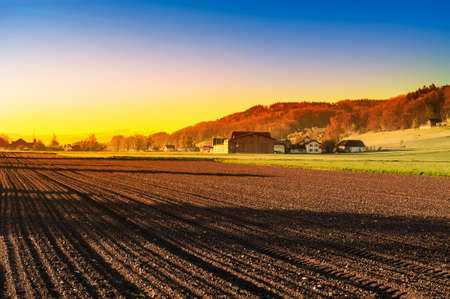 Swiss village surrounded by forests and plowed fields at sunset. Agriculture in Switzerland, arable land and pastures.