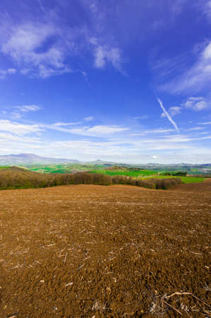 Plowed sloping hills of Tuscany in the spring. Rural landscape with field ready for sowing