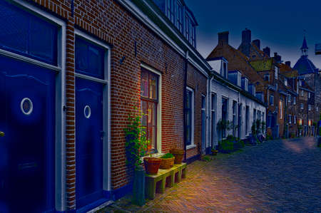 Typical Dutch brick houses in Holland at night. Street View with bikes parked in the historical center of Amersfoort in the Netherlands