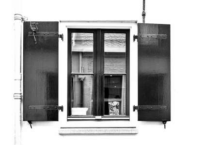 painted wood: Window with shutters in the wall of a house in Holland. Typical dutch house with windows painted in white and green. Black and white picture