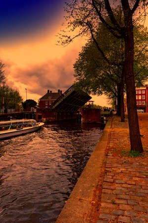 Tourist boat on the canal of Amsterdam in historic city centre at sunset. Amsterdam drawbridge in an half-open position while the water-bus is passing by.