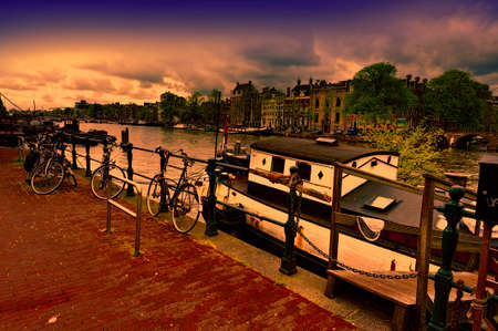 Urban scene in Amsterdam with houseboat and many bicycles at sunset. Street View with bikes parked on an embankment in the historical center of Amsterdam in the Netherlands