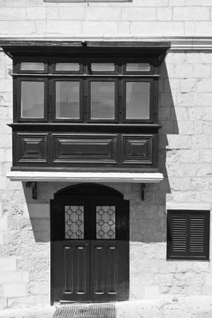 shutter: Building with traditional colorful maltese balcony and door in historical part of Valletta. Black and white picture