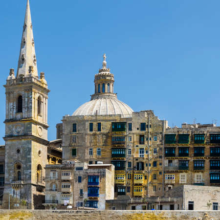 Cityscape view with Basilica of Our Lady of Mount Carmel on the island of Malta. Buildings with traditional colorful maltese balconies in historical part of Valletta.