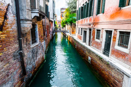 venice: Houses peeling off from dampness. Venice is situated across a group of islands that are separated by canals and linked by bridges. Gondola is a traditional, flat-bottomed Venetian rowing boat