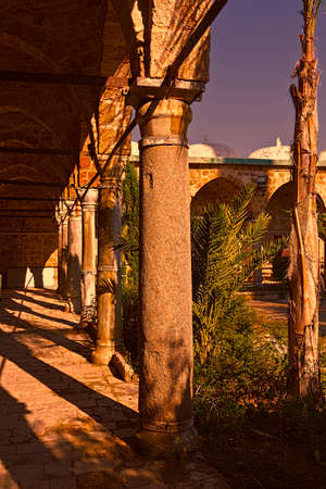 Garden in the courtyard of Muslim mosque in the old city of Akko at sunset. Al-Jazzar mosque as fine example of the Ottoman architecture in old Acre, Israel. Editorial