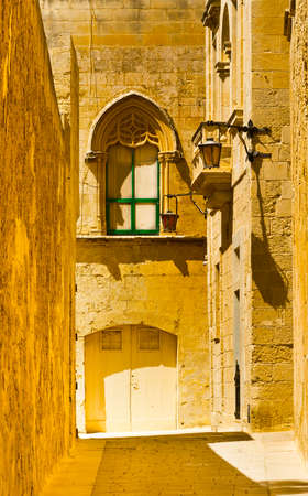 Narrow street with traditional maltese buildings in historical part of Mdina. The city was founded as Maleth in around the 8th century BC by Phoenician settlers on the island of Malta