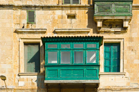 balcony: Building with traditional colorful maltese balcony in historical part of Valletta. Windows on the facade of a house in Malta