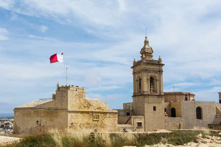 Victoria also known among the native Maltese as Rabat on island Gozo. View from Citadel to baroque Cathedral and flag of Malta