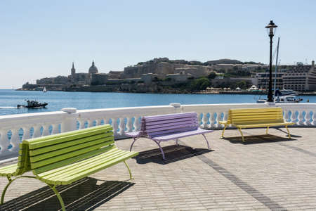 mediterranian home: Colorful park benches on the embankment of Valletta. Promenade on the background of the bay in Malta