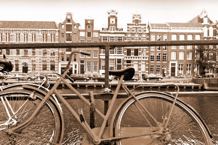 Street View with bike parked on an embankment in the historical center of Amsterdam in the Netherlands. Vintage Style Sepia photo