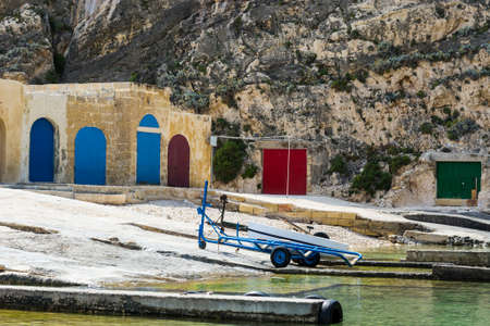 Boat on the trolley for launching on the water near hangars. The Inland Sea is a lagoon of seawater on the island of Gozo linked to the Mediterranean Sea through a narrow natural arch. Stock Photo