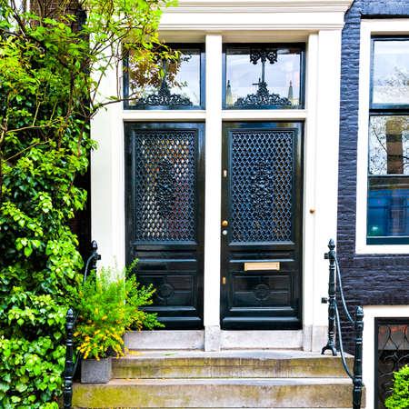 Geschilderde deur van het traditionele huis in Amsterdam. Baksteenvoorgevel van het oude stadshuis in Holland. Stockfoto