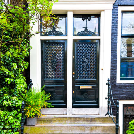 Painted door of the traditional house in Amsterdam. Brick facade of the old city house in Holland. Zdjęcie Seryjne