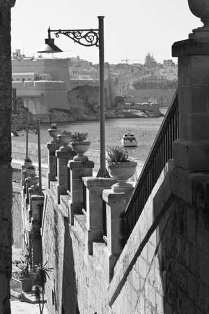 Street along the wall of fortress leading to the sea on the island of Malta in historical part of Valletta. Black and white picture