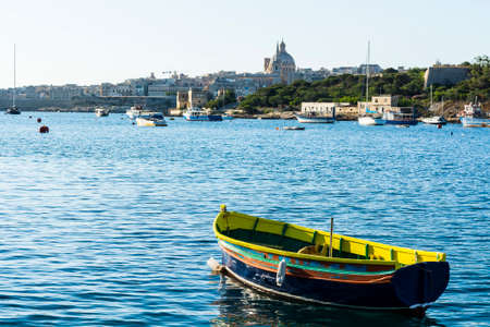 Cityscape view with Basilica of Our Lady of Mount Carmel on the island of Malta. Yachts docked at the port of Valletta. A shabby old boat among the luxury ships