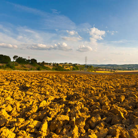Plowed sloping hills of tuscany in the autumn. Rural landscape with field after harvest. High voltage line and power pylons on the plowed field in Italy