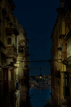 Typical narrow street leading to the sea on the island of Malta at night. Buildings with traditional colorful maltese balconies in historical part of Valletta.