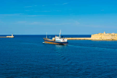 Cargo ship leaves the harbor of Valletta. Lighthouses indicate the entrance to the ports of Malta