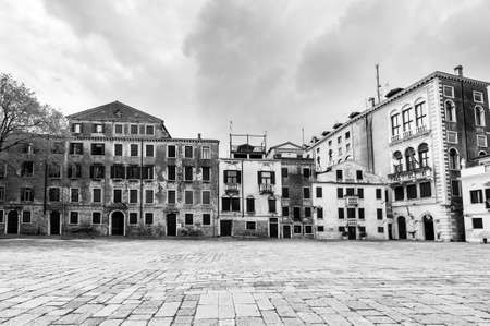 linked: Houses peeling off from dampness. Venice is situated across a group of islands that are separated by canals and linked by bridges. Black and white picture Stock Photo