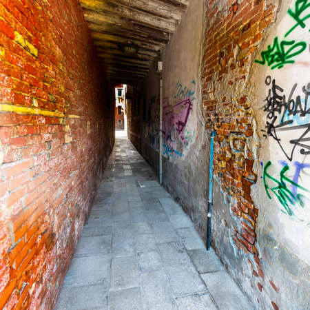 Narrow passage between old houses in Venice. Street with archway in the medieval italian town. Stock Photo