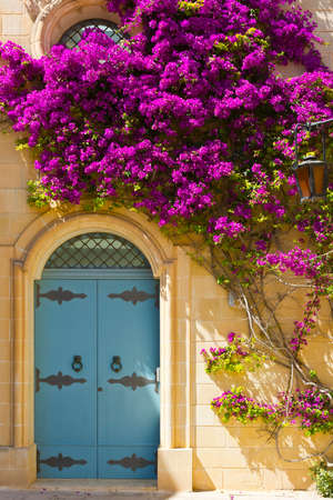Building with traditional maltese door decorated with fresh flowers in Mdina. Stock Photo