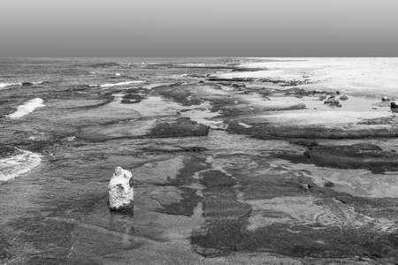 Israeli shore of the Mediterranean Sea. Rocky beach in Israel. Black and white picture