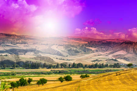 Wheat fields in Sicily after harvesting. Sicilian landscape at sunrise, hills, flowers, pasture and sunlight