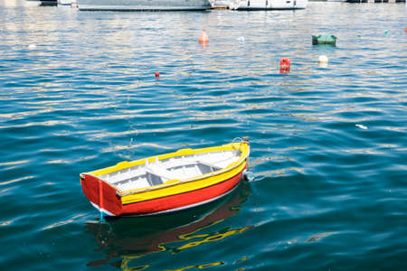 Colored buoys floating in port of Malta for mooring of yachts. A wooden cheap boat among the luxury ships Stock Photo