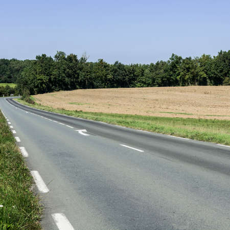 Asphalt road between autumn plowed fields in France after harvest Stock Photo