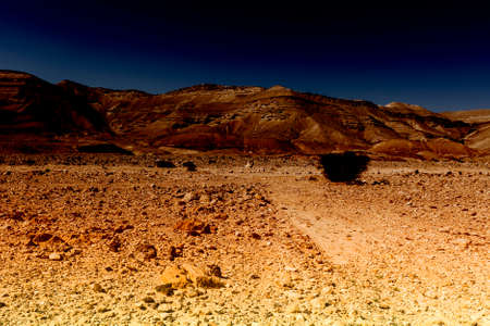 Rocky hills of the Negev Desert in Israel early in the morning. Breathtaking landscape at sunrise, desert rock formations, dusty mountains, wadis  and deep craters.