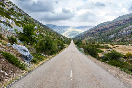 Stright asphalt road of Europe Peaks in Spain on a rainy day Stock Photo