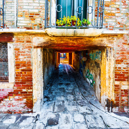 Narrow passage between old houses in Venice. Street with archway in the medieval italian town.