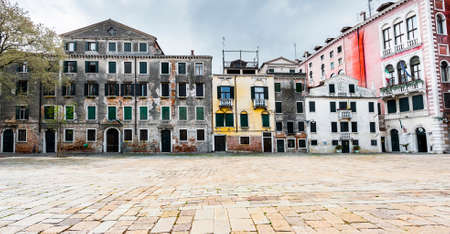 Houses peeling off from dampness. Venice is situated across a group of islands that are separated by canals and linked by bridges. Stock Photo