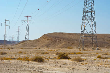 Desolate infinity of the Rocky hills of the Negev Desert in Israel. Electrical power lines on pylons in the landscape of the Middle East