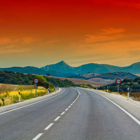 Asphalt road between fields in Spain after harvesting at sunrise. Breathtaking landscape and nature of the Iberian Peninsula Stock Photo