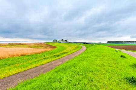 Agriculture on Land Reclaimed from the See in Netherlands. Asphalt road along protective dam and canal in Holland Stockfoto - 109015646