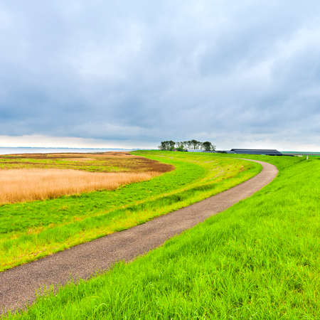 Agriculture on Land Reclaimed from the See in Netherlands. Asphalt road along protective dam and canal in Holland