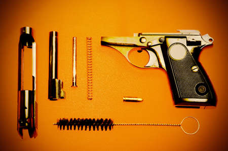 Disassembled pistol and cartridge to it on a red background. Retro style Stock Photo