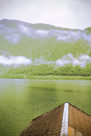 Rain and clouds on the Hallstattersee in Austria. Morning mist over the Austrian landscape with lake, forests, fields, pastures, meadows and tile roofs. Vintage style