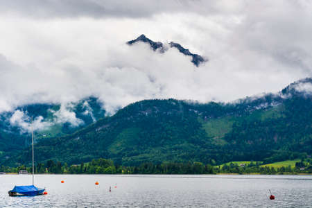 Rain and clouds on the Wolfgangsee in Austria. Morning mist over the Austrian landscape with lake, yacht, forests,  pastures, meadows and villages