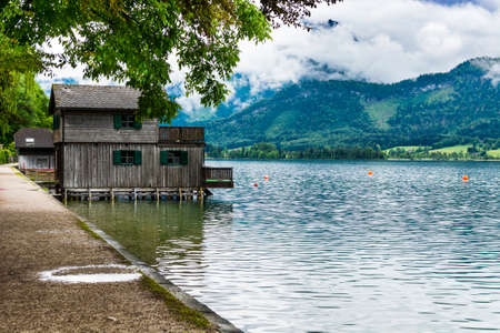 Rain and clouds on the Wolfgangsee in Austria. Morning mist over the Austrian landscape with lake, boat hangars, forests,  pastures, meadows and villages