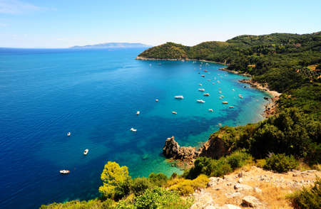 Italian seascape with yachts in harbor, green hills and indented coastline. Retro style
